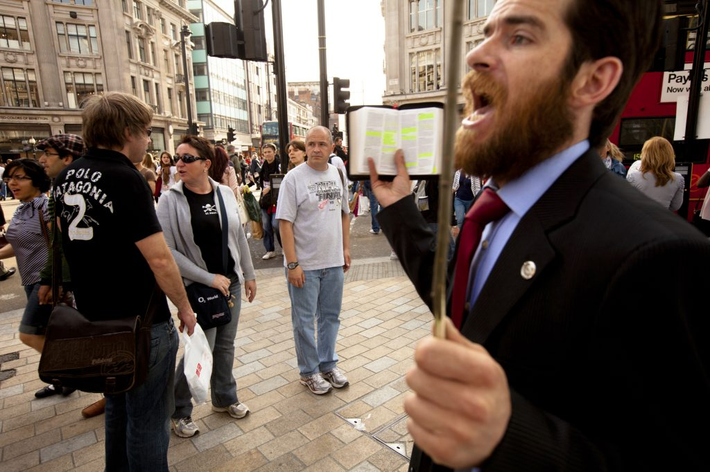 """London, UK - May 6, 2011: An Evangelical street preacher reads from a bible, occasionally stopping to shout personally directed remarks at bewildered and at time aggravated pedestrians in the busy Oxford street shopping district of London."""